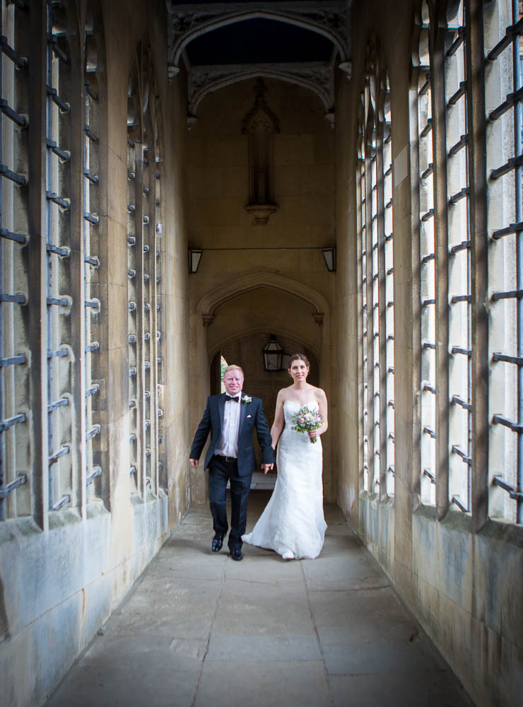 Bride and groom walking along the Bridge of Sighs - Photographed during a St John's College Wedding