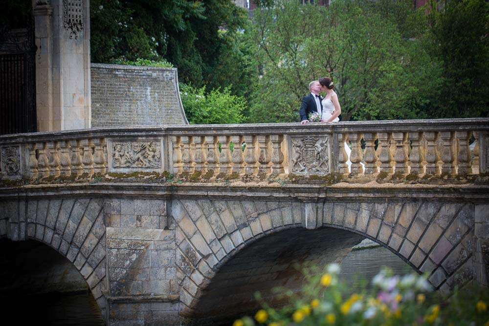 Bride and groom kissing on a bridge in St John's College, photographed by Juan Muino Wedding Photographer during a St John's College Wedding