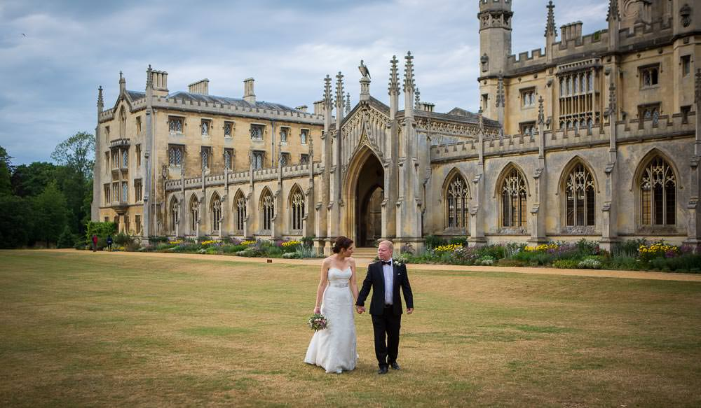 Bride and groom walking on lawns with St John's College in the background