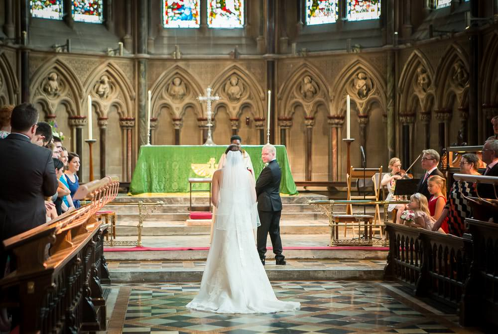 Groom looking towards bride in chapel at St John's College Wedding