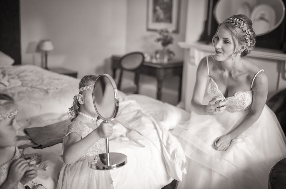 Bride spraying perfume whilst flower girl holds a mirror. photographed in black and white by Cambridge Wedding Photographer