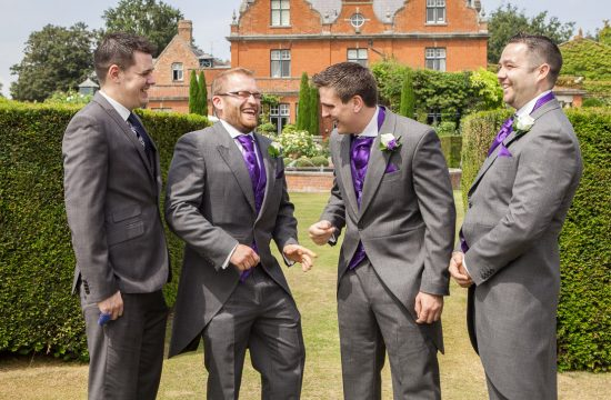 Groom and party laughing together in front of Chippenham Park Wedding