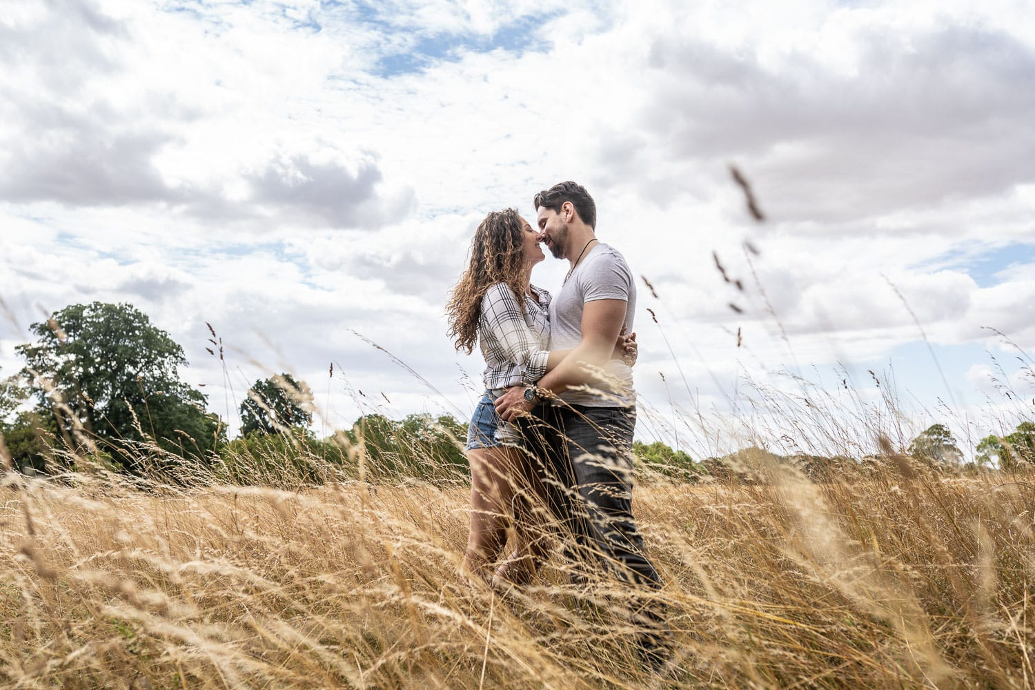 Couple embracing in a meadow during their pre-wedding shooting in Cambridge