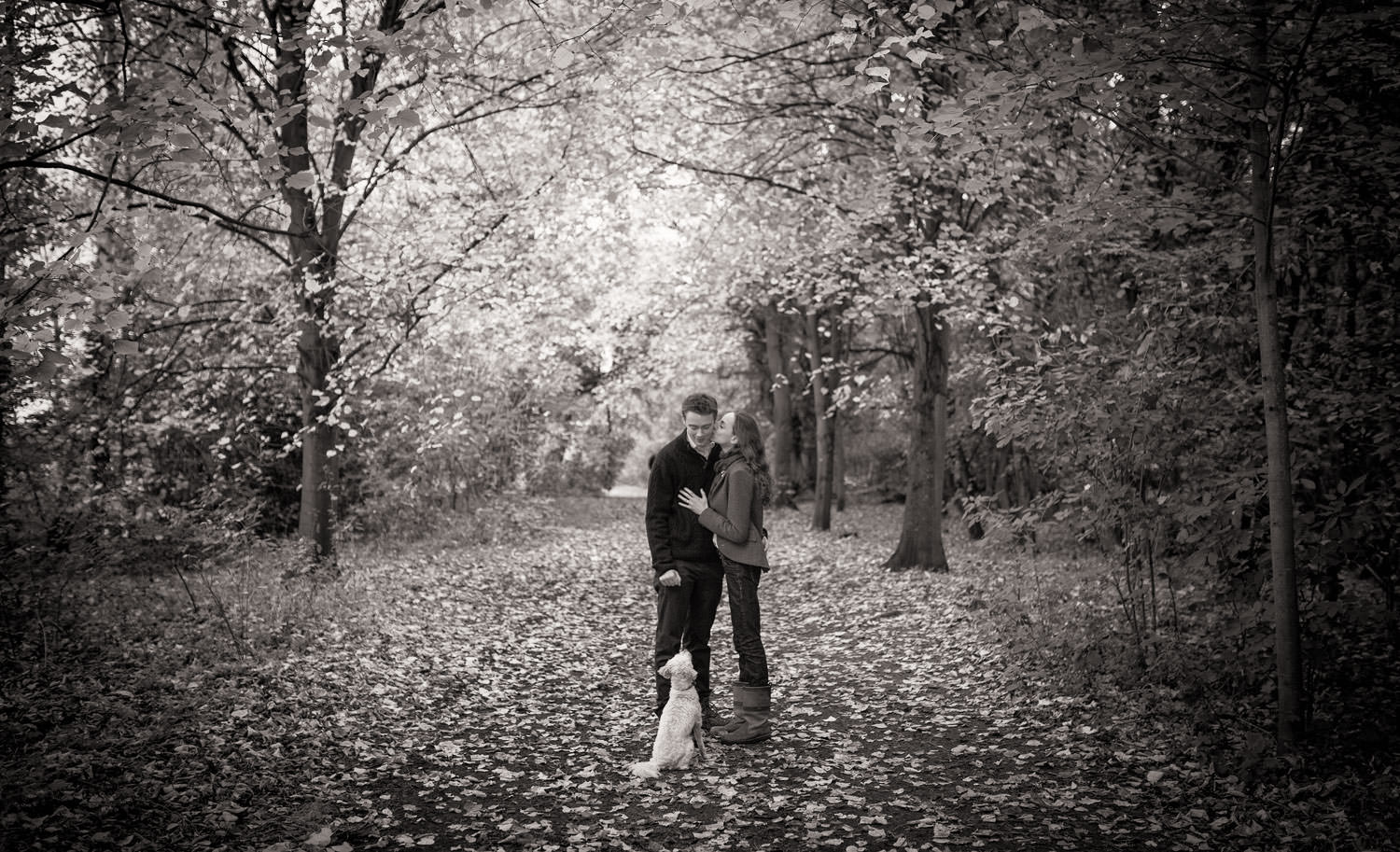 Young couple standing in woods with their white dog during an engagement shoot