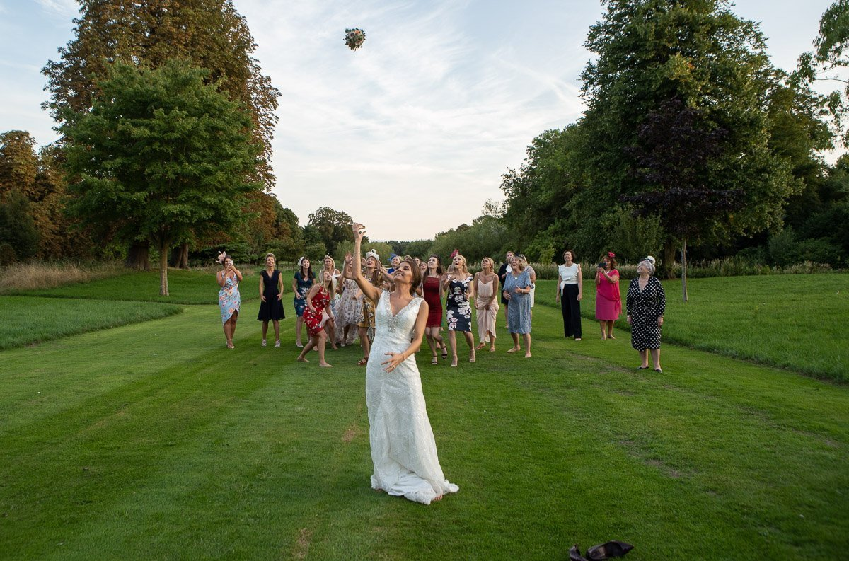 Bride throwing her bouquet at Chippenham Wedding
