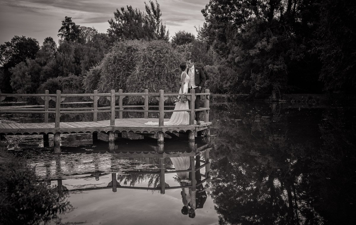 Black and white image of bride and groom standing near the lake at Chippenham Wedding