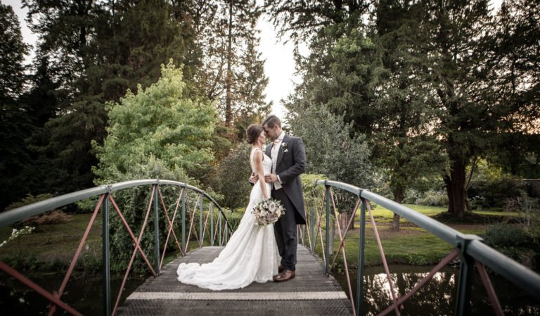 Bride and Groom standing on a bridge at Chippenham Park Wedding
