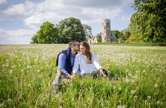 Couple sitting i a meadow during their pre-wedding shoot in Cambridge