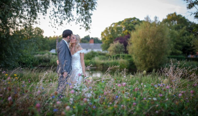 Bride and Groom kissing standing in a wild flower meadow at The Granary Estates