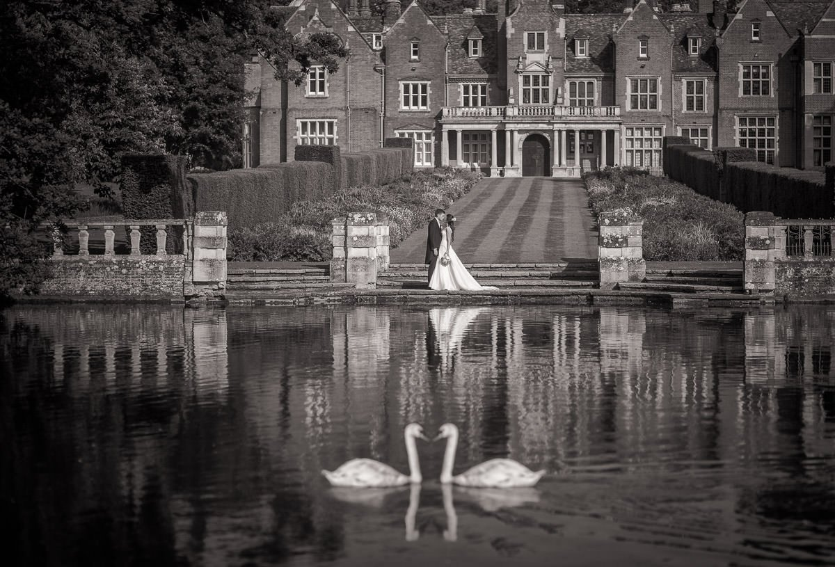 Black and white shot of brie and groom standing in front of Longstowe Hall with swans in foreground