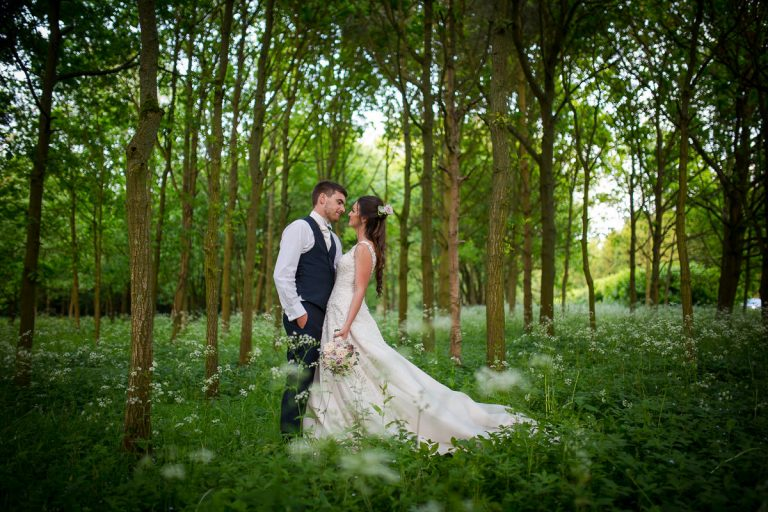 Bride and groom kissing in a meadow at twilight at Longstowe Hall