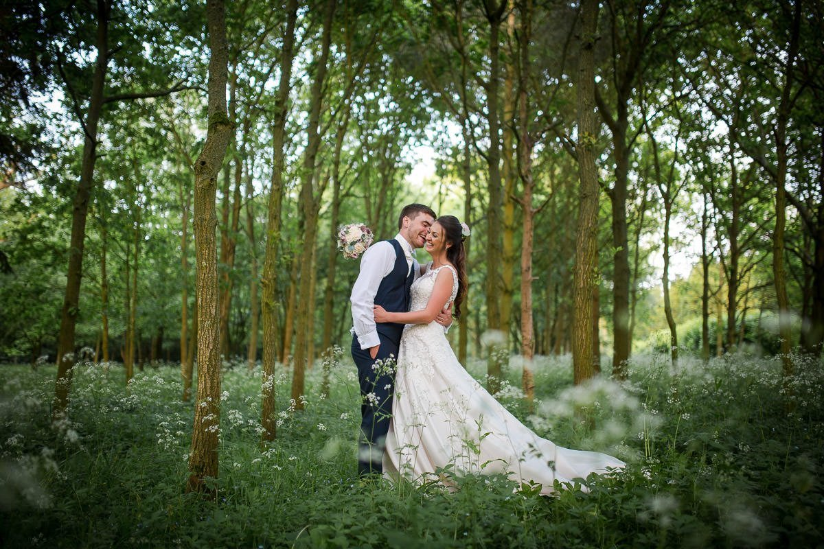 Bride and groom kissing in a meadow at Longstowe Hall, with out of focus cow slips in the foreground. wedding photography.