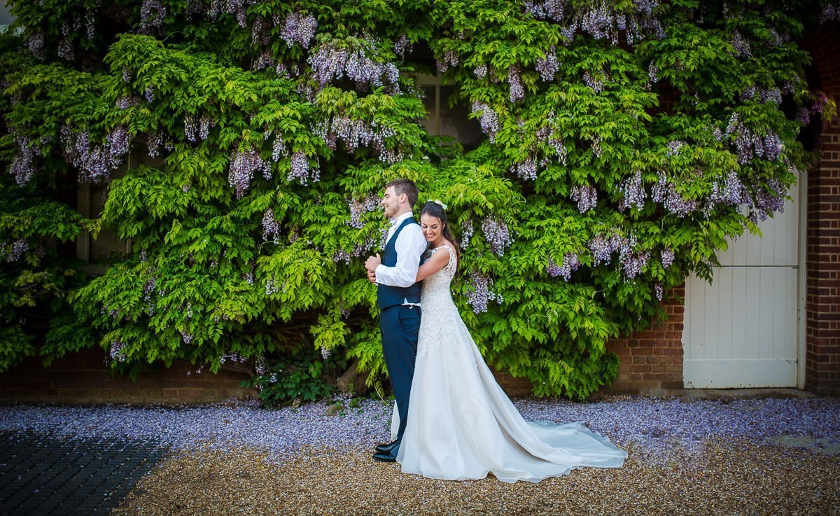 Bride and groom standing infront of wisteria at Longstowe Hall