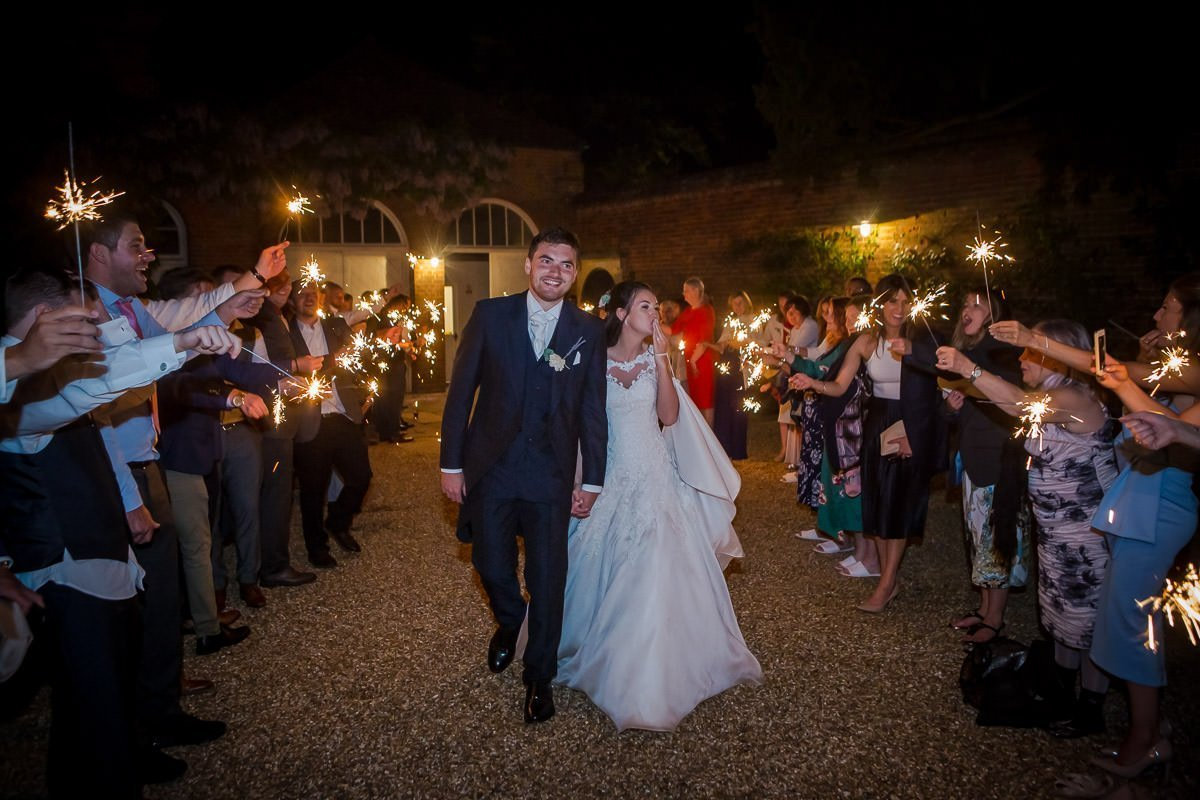 Bride and groom walking through sparkler parade at Longstowe Hall