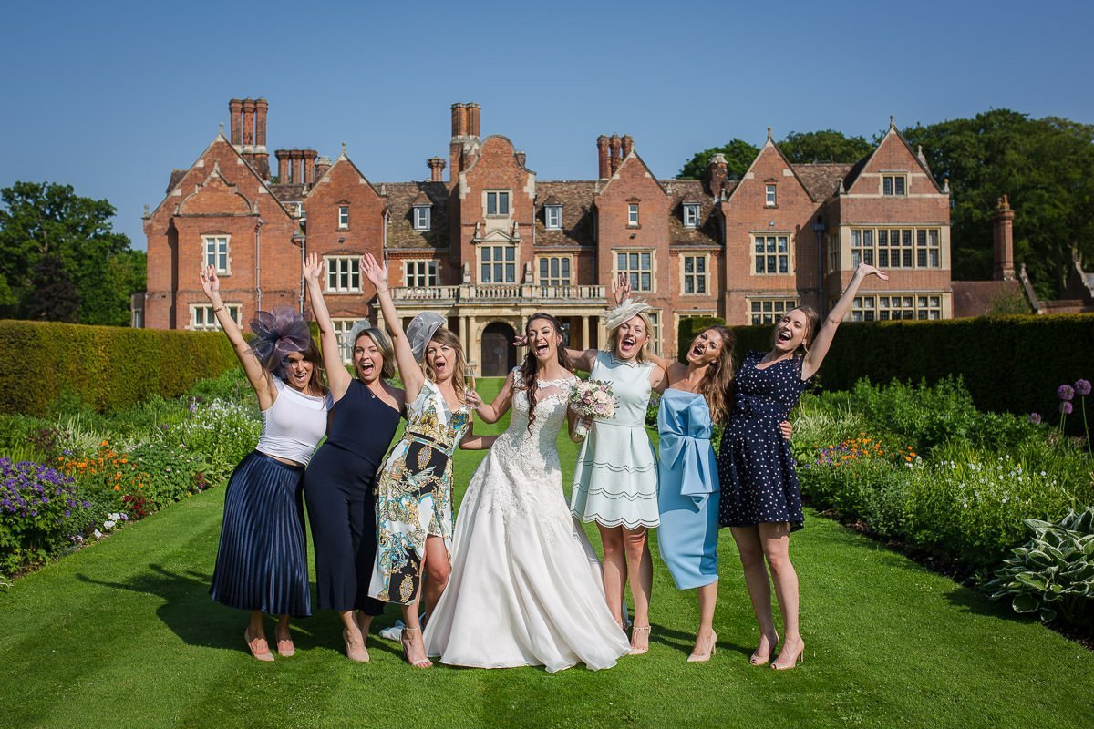 Bride and friends celebrating in front of Longstowe Hall