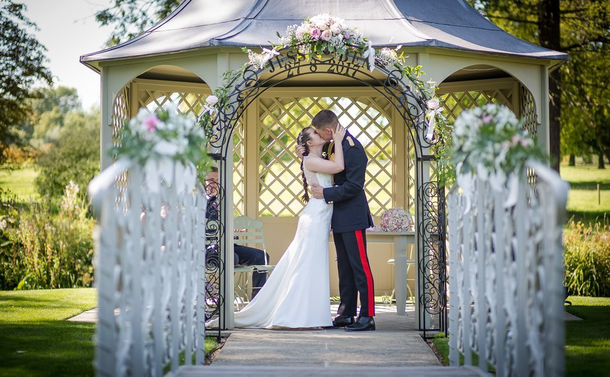 bride and groom kissing in ceremony at Longstowe Hall
