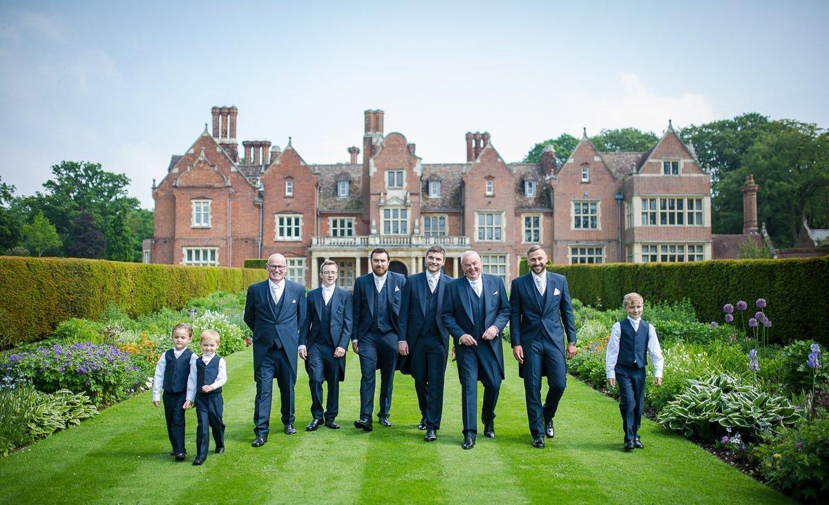Colour shot of grooms part walking in Longstowe Hall