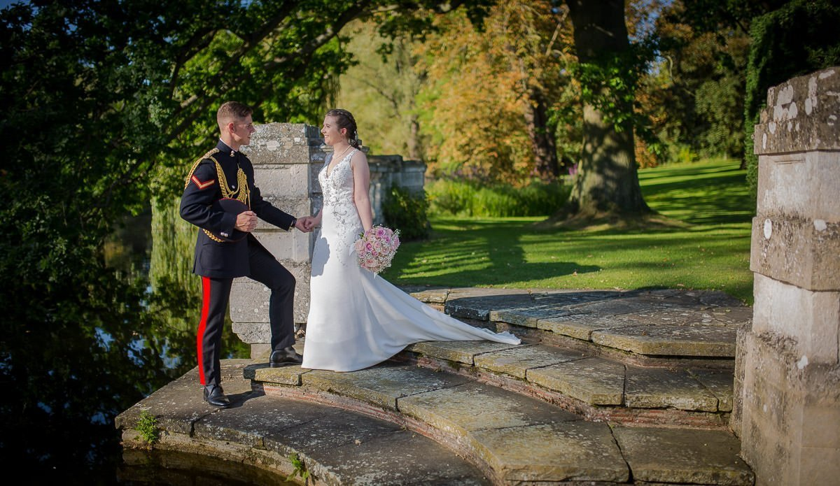 Groom helping bride walk down steps at Longstowe Hall