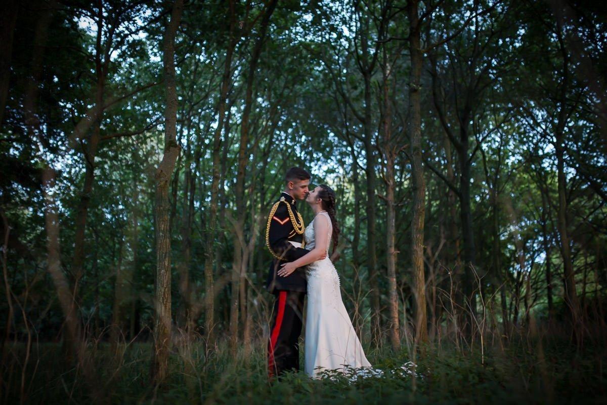 Groom in uniform kissing his bride at Longstowe Hall