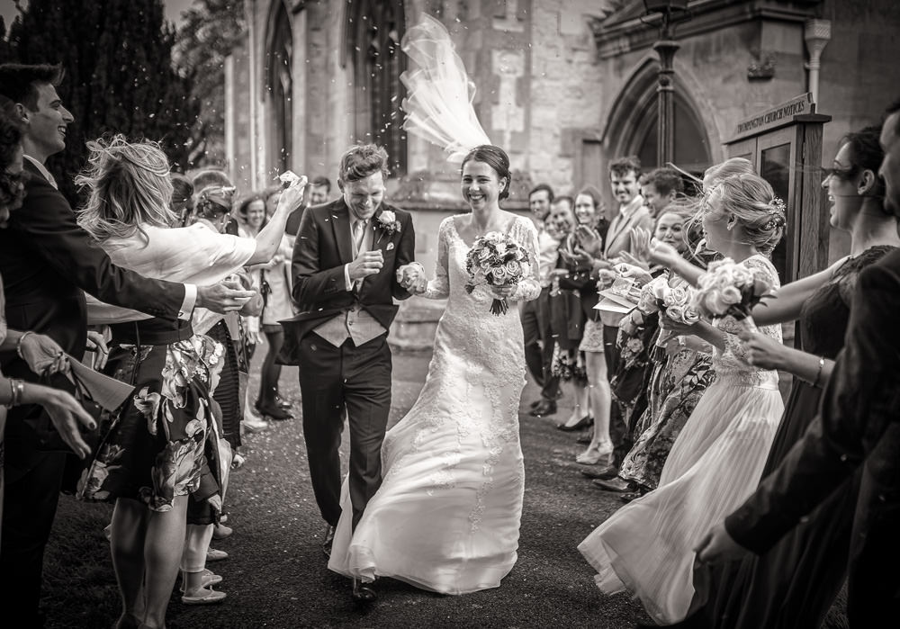 wedding photographer cambridge 's shot of a bride and groom walking in a confetti on a blustery windy day.