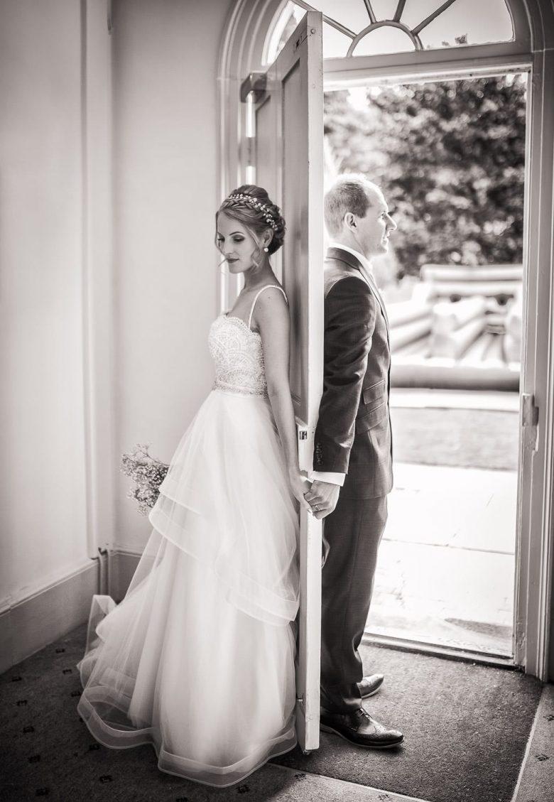 Bride and groom standing by a door holding hands.