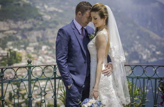 Bride and Groom standing by an ornate fence, in Positano.