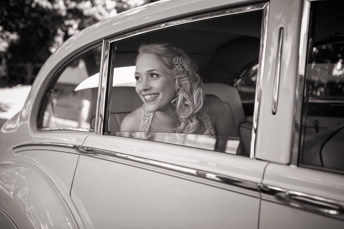 Bride lookingout of her bridal car and smiling, part of the black and white wedding photographs collection.