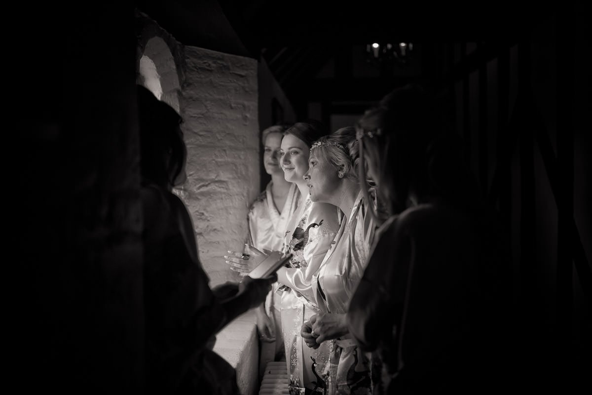 bridesmaids looking out of window, photographed in black and white as black and white wedding photographs collection.