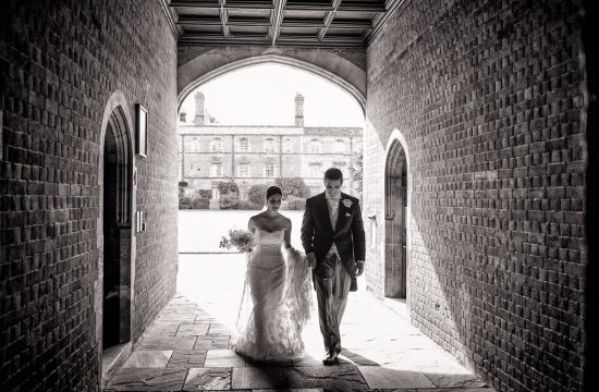 Black and White wedding photography photograph of bride and groom walking through the cloisters at Kings College Cambridge