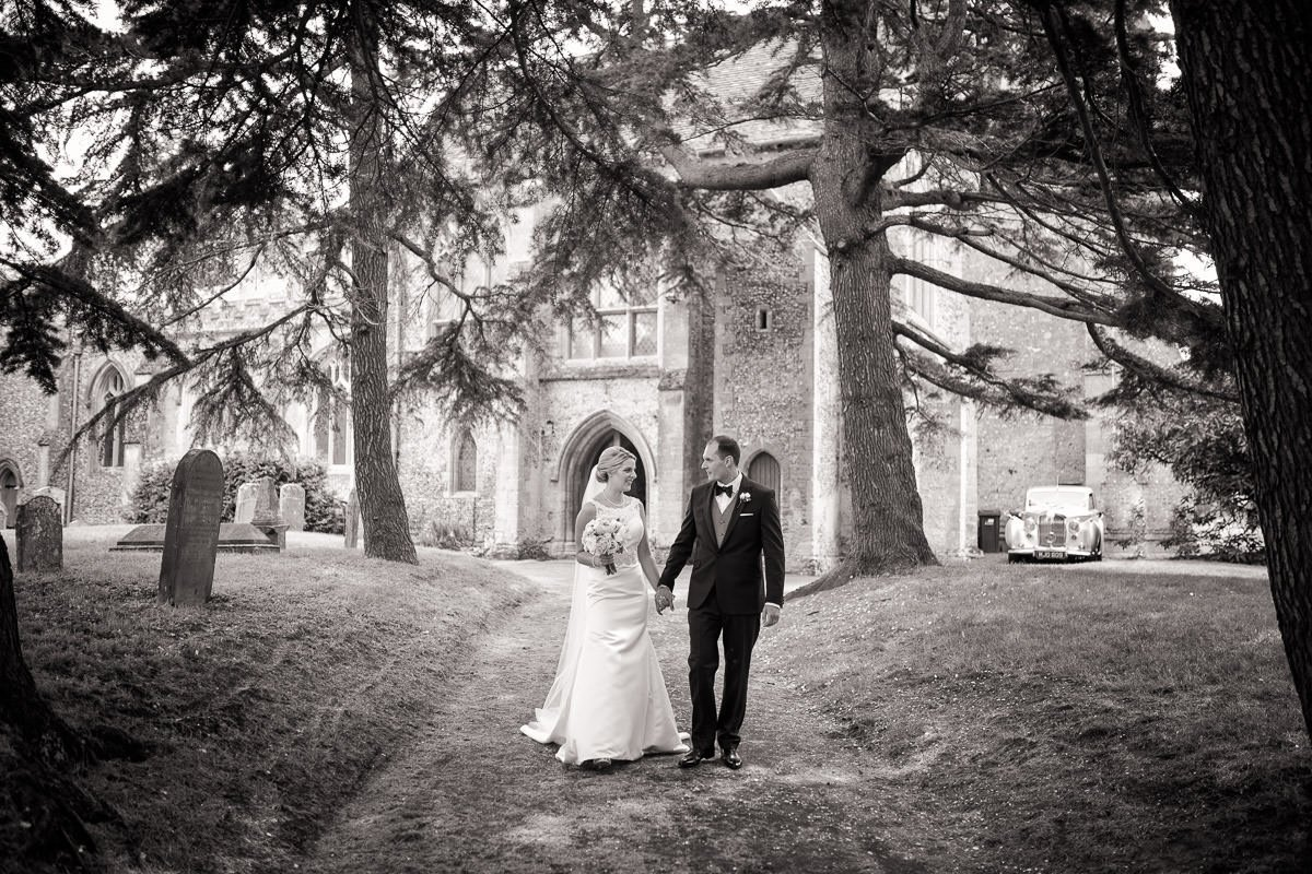 One of a collection of black and white wedding photographs showing a bride and groom walking away from the church.