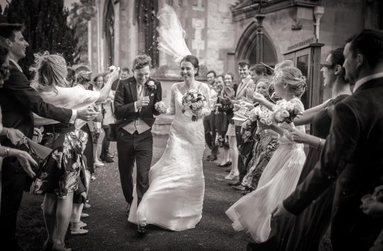Bride and Groom walking through confetti on a windy day, with brides veil caught in the wind