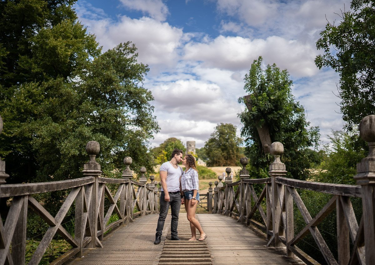 Couple standing on old wooden bridge with a folly behind photographed during their pre-wedding shoot in Cambridge