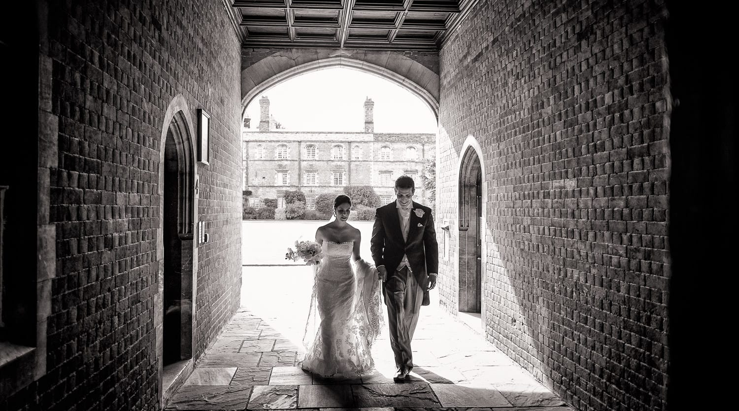 Bride and groom walking through Kings College, Cambridge, Natural Wedding Photography