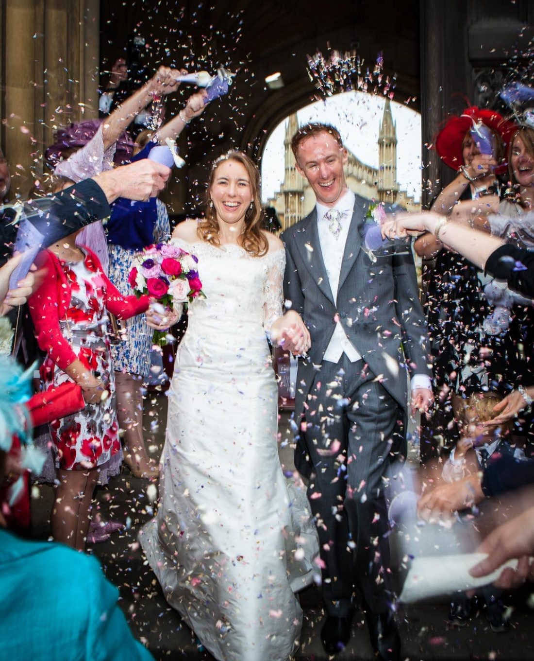 Bride and Groom walking through confetti at Corpus Christie College wedding. Natural Wedding Photography