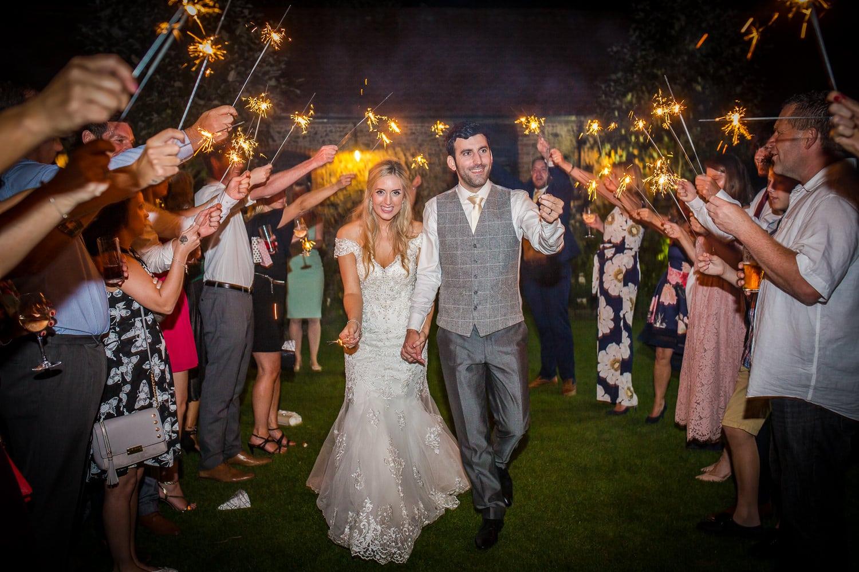 Bride and Groom walking through a sparkler parade