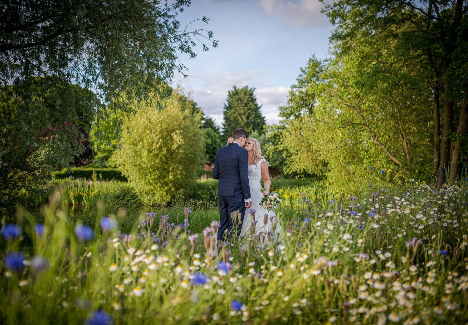 Bride and groom standing in a meadow of wild flowers at Granary Barns, Wedding Photography
