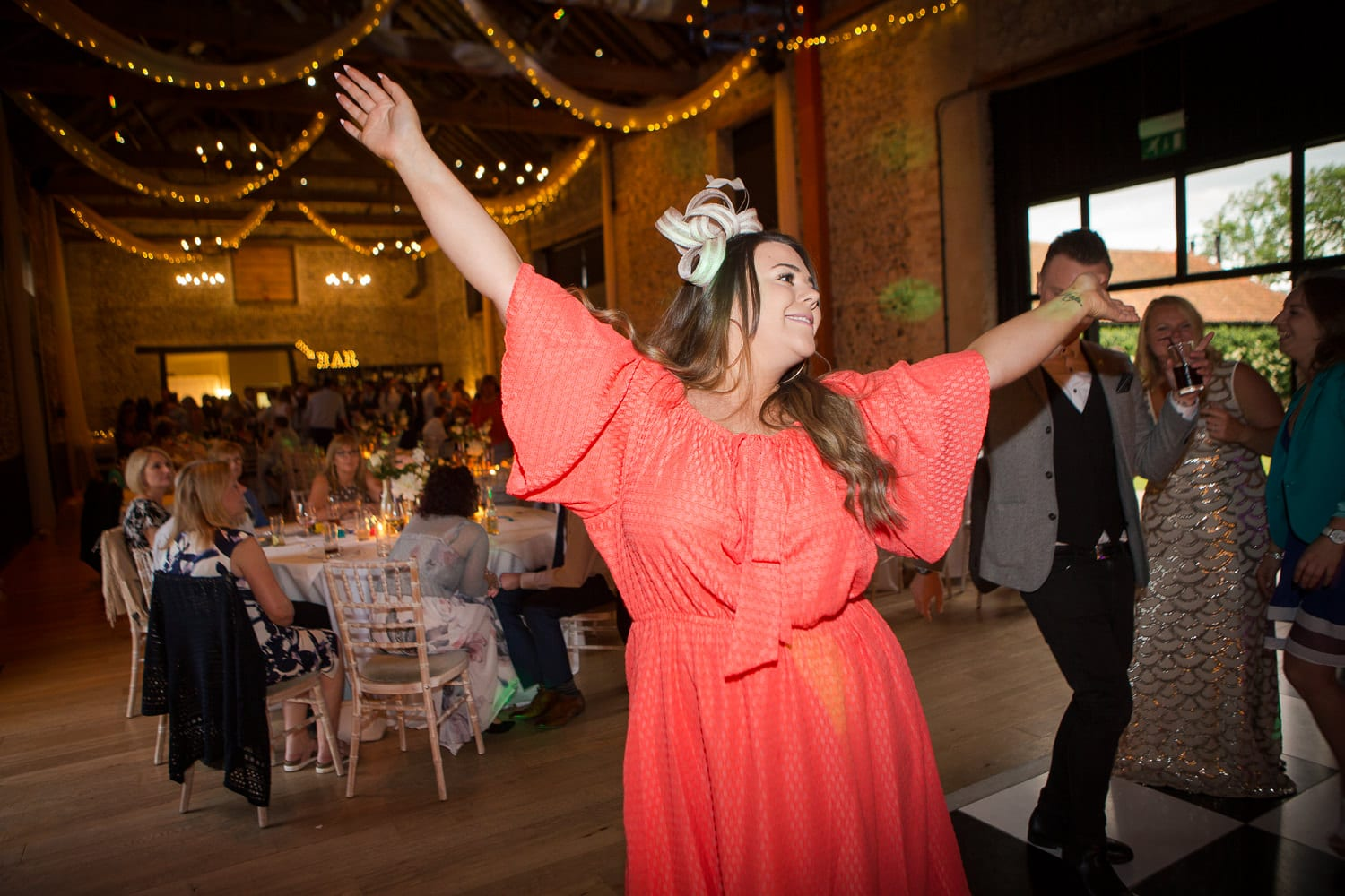 Wedding guest in red dress dancing at Granary Barns Wedding