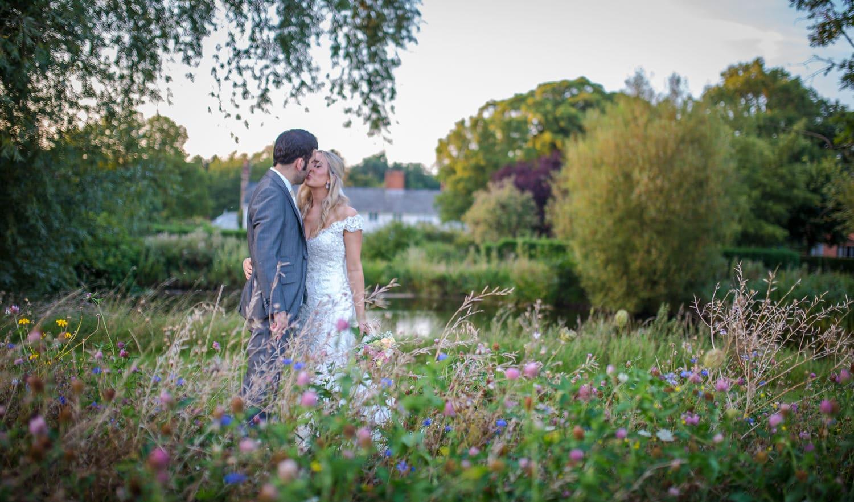 Bride and Groom standing in a meadow of wild flowers. Granary Barns Weddings