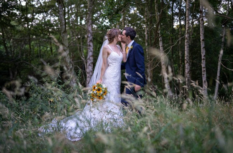 bride and groom kissing each other in a meadow