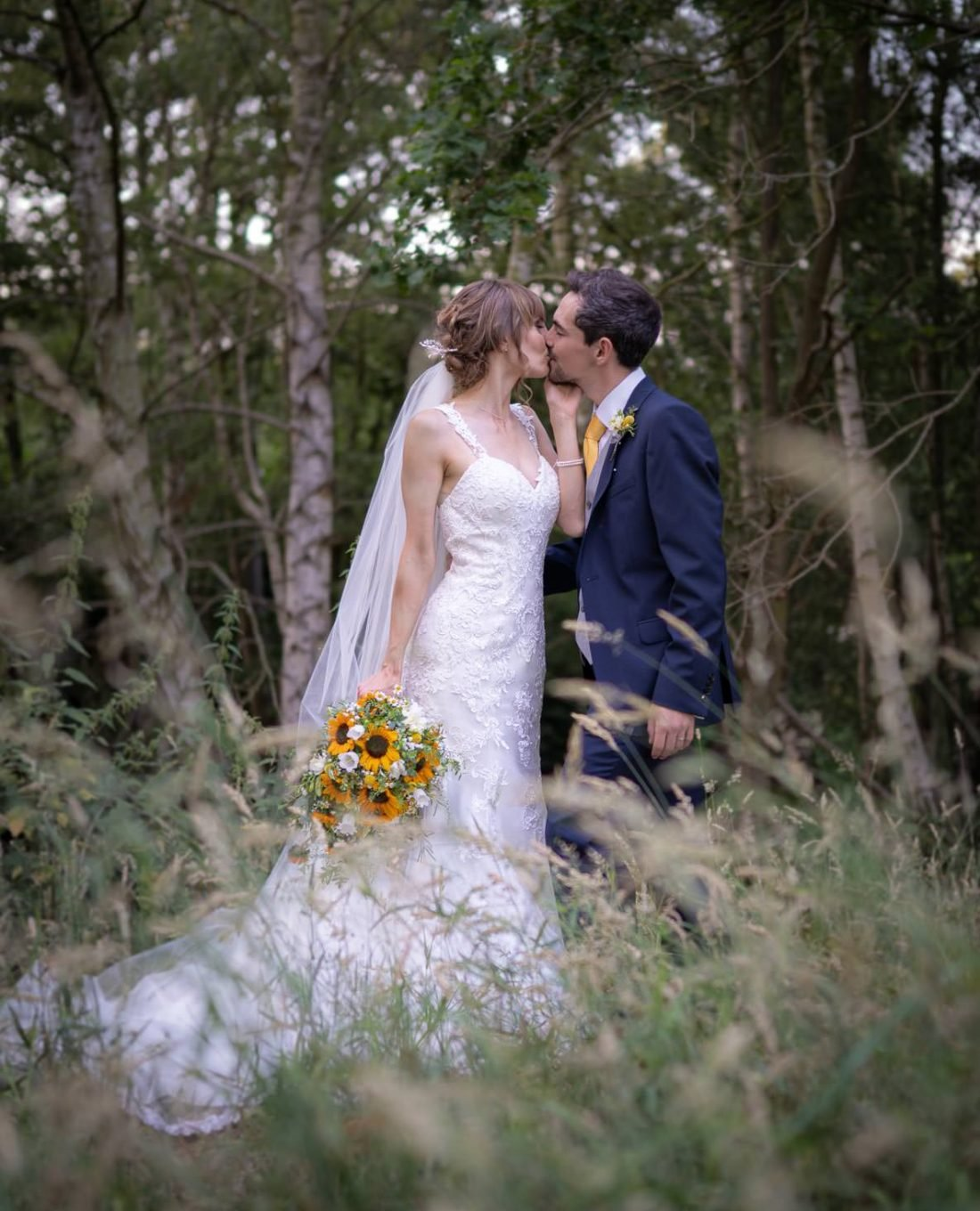 Bride and groom kissing in a meadow of wild grasses