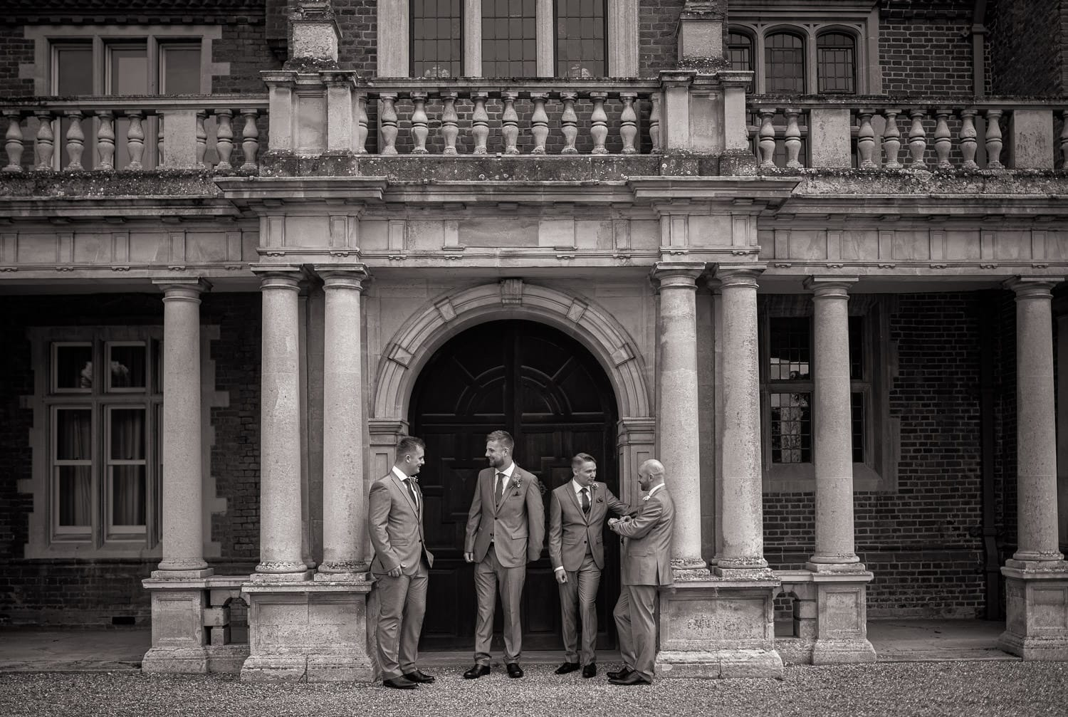 Grooms and party standing at Longstowe Hall Weddings in black and white