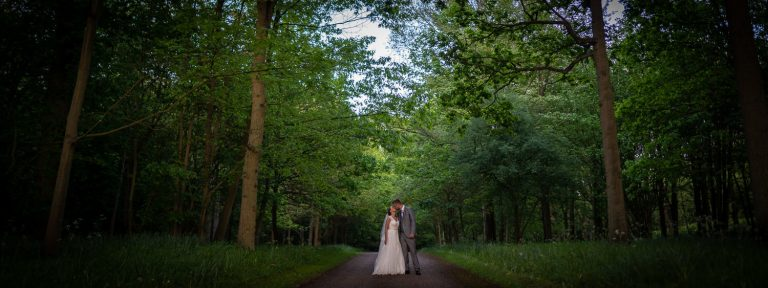 Bride and groom standing together in a tree lined avenue at Longstowe Hall Weddings