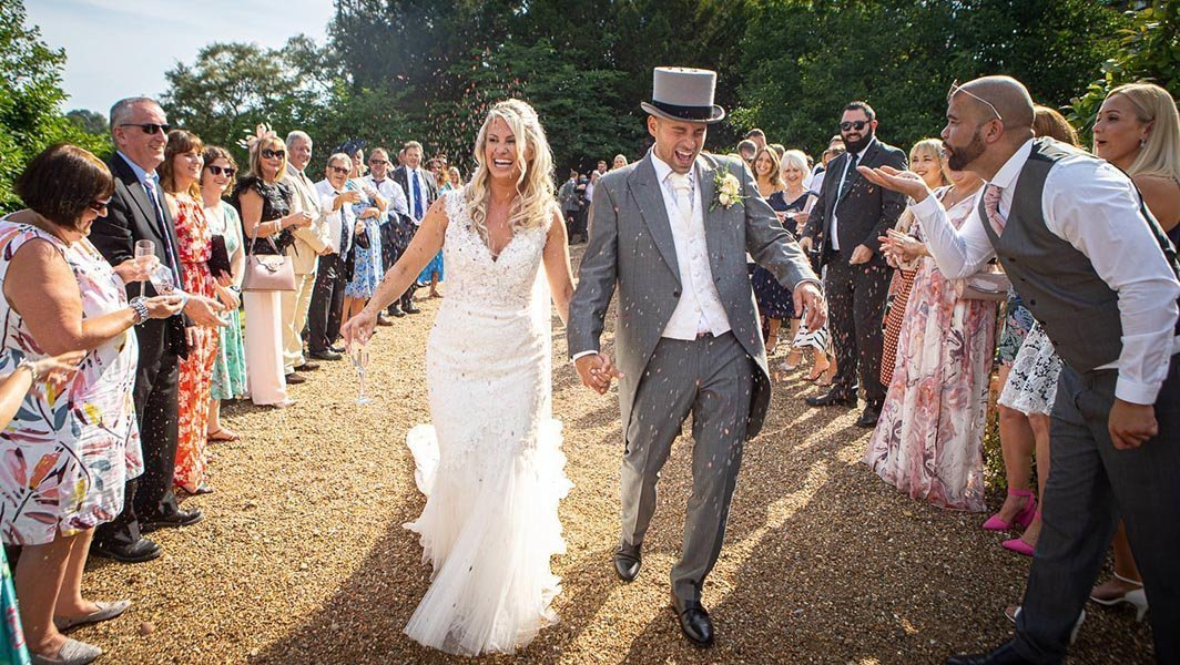 Love this shot of our bride and groom having so much fun as they walk through their confetti parade
