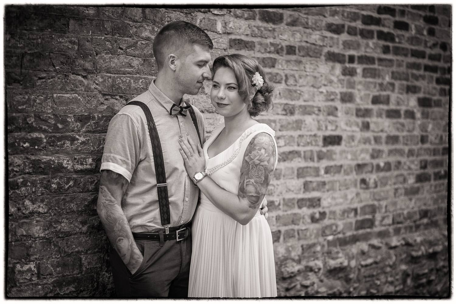 A favourite shot in black and white from a pre-wedding shoot photographed in cambridge. Couple are leaning against a brick wall during their shoot.