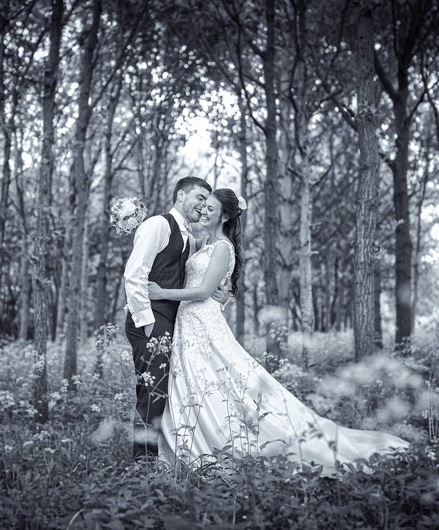 Bride and groom photographed at longstowe hall in the woodlands, with cowslips in front -black and white image - cambridge wedding photographers