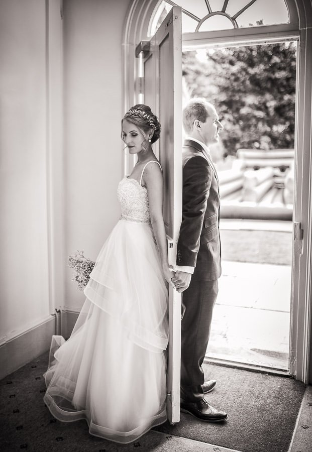 Bride and groom holding hands behind a door at a Cambridge Wedding