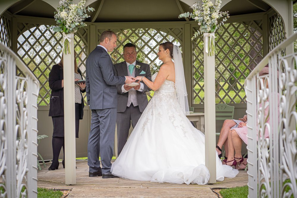 Wedding ceremony with bride and groom exchanging rings at Longstowe Wedding