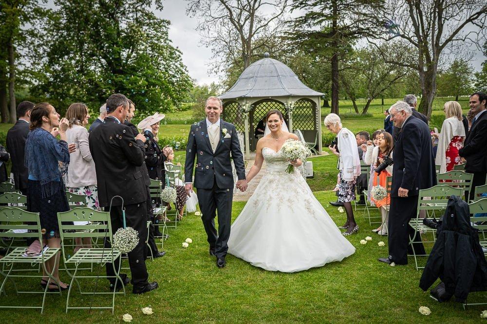 Bride and groom walking through guests during their Longstowe