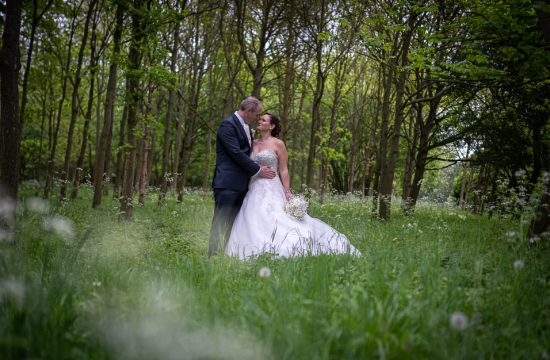 Bride and groom hugging in a wild flower meadow