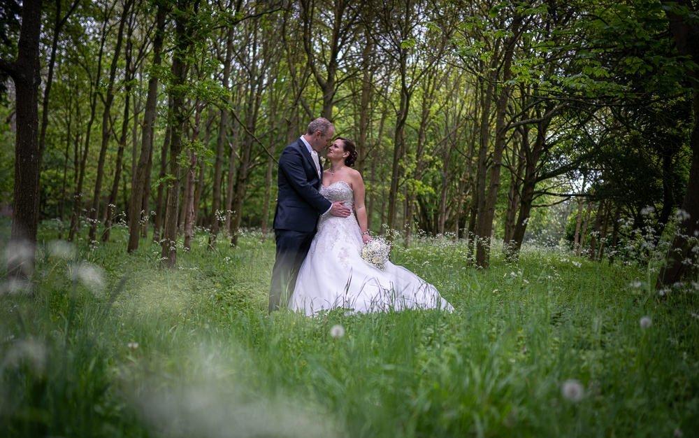 Bride and groom hugging in a wild flower meadow